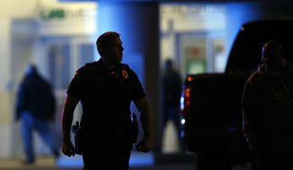 Authorities respond to a gunman that opened fire at a Birmingham, Alabama, hospital, wounding two men before turning the gun on himself Wednesday night, police said on Wednesday, March 14, 2018, in Birmingham, Ala. (AP Photo/Brynn Anderson)