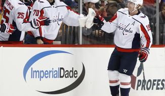 Washington Capitals center Nicklas Backstrom (19), of Sweden, is congratulated by right wing Devante Smith-Pelly (25) and goaltender Braden Holtby (70) after scoring during the second period of an NHL hockey game against the New York Islanders in New York, Thursday, March 15, 2018. (AP Photo/Kathy Willens)
