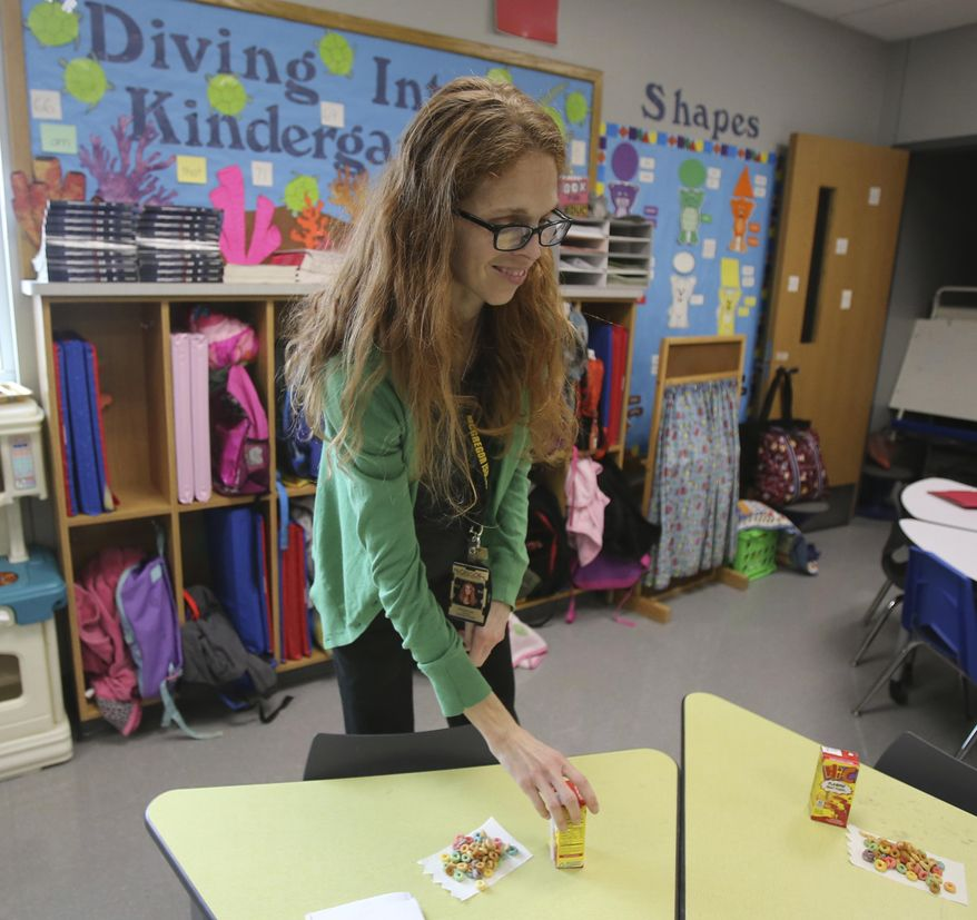 In this Wednesday, Feb. 28, 2018 photo, Michelle Porter prepares her kindergarten classroom  in McGregor, Texas. Porter was a senior at Columbine High School when two students killed 13 others in 1999. Now into her second year as a teacher at McGregor Primary School, when Porter sees headlines about school shootings, she tries not to think about the possibility of facing a similar situation again. (Jerry Larson/Waco Tribune Herald, via AP)