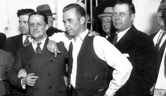 John Dillinger, center, strikes a pose with Lake County prosecutor Robert Estill, left, in the jail at Crown Point, Ind., in 1934. Dillinger was awaiting trial for the murder of police officer Willliam Patrick O'Malley when Dillinger robbed the First National Bank of East Chicago on Jan. 15, 1934. Dillinger was among the gangsters mentioned as Congress debated the first significant federal gun control law, the National Firearms Act of 1934. (AP Photo) ** FILE **