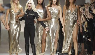 FILE - In this Friday, Sept. 22, 2017 file photo, Claudia Shiffer, Donatella Versace, Naomi Campbell, Cindy Crawford and Helena Christensen on the catwalk at the end of the Versace women's Spring/Summer 2018 fashion collection, presented in Milan, Italy. Versace has become the latest fashion house to eliminate fur from its collections, joining Gucci, Giorgio Arman, Hugo Boss among others. (AP Photo/Luca Bruno, file)