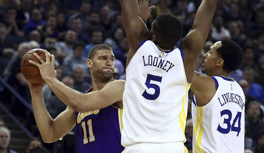 Los Angeles Lakers' Brook Lopez, left, looks to pass away from Golden State Warriors' Kevon Looney (5) and Shaun Livingston (34) during the first half of an NBA basketball game Wednesday, March 14, 2018, in Oakland, Calif. (AP Photo/Ben Margot)
