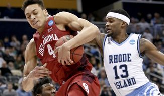 Oklahoma's Jamuni McNeace (4) grabs a rebound in front of Rhode Island's Stanford Robinson (13) during the first half in the first round of the NCAA men's college basketball tournament, Thursday, March 15, 2018, in Pittsburgh. (AP Photo/Keith Srakocic)