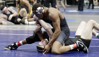 Ohio State's Myles Martin, top, controls Iowa's Mitchell Bowman during a bout a 184 pounds in the NCAA Division I wrestling championships Thursday, March 15, 2018, in Cleveland. (AP Photo/Tony Dejak)