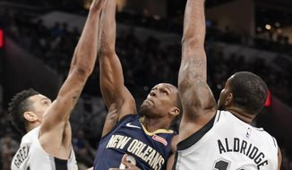 New Orleans Pelicans' Rajon Rondo, center, shoots against San Antonio Spurs' LaMarcus Aldridge (12) and Danny Green during the first half of an NBA basketball game, Thursday, March 15, 2018, in San Antonio. (AP Photo/Darren Abate)