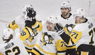 Pittsburgh Penguins right wing Patric Hornqvist (72) celebrates with left wing Carl Hagelin (62), defenseman Kris Letang (58) and center Evgeni Malkin (71) after scoring against the Montreal Canadiens during the third period of an NHL hockey game Thursday, March 15, 2018, in Montreal. (Graham Hughes/The Canadian Press via AP)