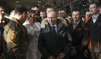 FILE - In this Tuesday, March 6, 2018 file photo, Russian President Vladimir Putin listens to employees of Uralvagonzavod factory in Nizhny Tagil, Russia. President Vladimir Putin seems self-assured and confident of victory in the election on Sunday, March 18, even as the Kremlin works hard to bolster turnout to make the result as impressive as possible. Unlike the 2012 balloting when he often looked tense and nervous amid massive protests of his rule, Putin faces no such threats this time, despite an anemic economy and spiraling tensions with the West. (AP Photo/Alexander Zemlianichenko, File)