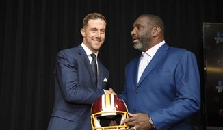 Newly signed Washington Redskins quarterback Alex Smith, left, shakes hands and poses with Doug Williams, the NFL football team's senior vice president of player personnel, during a news conference Thursday, March 15, 2018, in Ashburn, Va. (AP Photo/Nick Wass) ** FILE **