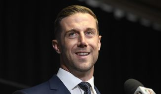 Newly signed Washington Redskins quarterback Alex Smith smiles during the NFL football team's news conference Thursday, March 15, 2018, in Ashburn, Va. (AP Photo/Nick Wass)