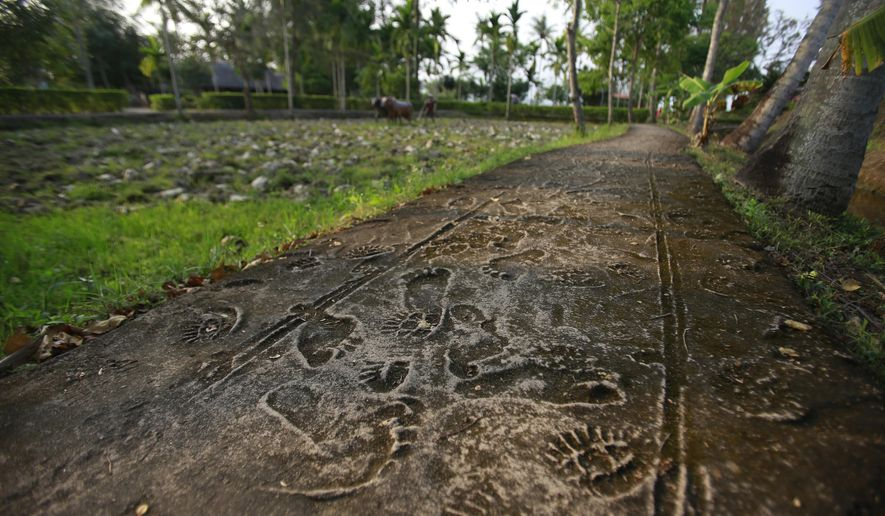 In this Wednesday, March 14, 2018, photo, foot prints of villagers and U.S soldiers' combat boots are reconstructed in My Lai memorial site in Son My, Vietnam. On March 16, 1968, U.S soldiers of Charlie Company, sent on what they were told was a mission to confront a crack outfit of their Vietcong enemies, met no resistance, but over the course of three to four hours killed 504 unarmed civilians, mostly women, children and the elderly, in My Lai and a neighboring community. (AP Photo/Hau Dinh)