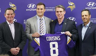 Minnesota Vikings new quarterback Kirk Cousins, second from left, poses with his new jersey along with, from left, head coach Mike Zimmer, general manager Rick Spielman and owner Mark Wilf after Cousins was introduced during a news conference, following signing a three-year, $84 million contract at the NFL football team's new headquarters Thursday, March 15, 2018, in Eagan, Minn. (AP Photo/Jim Mone)
