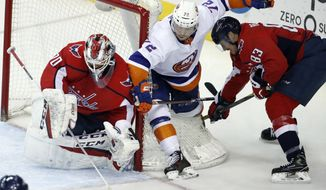 Washington Capitals goaltender Braden Holtby (70) knocks the puck away from New York Islanders center Anthony Beauvillier (72) as Washington Capitals center Jay Beagle (83) defends, in the third period of an NHL hockey game, Friday, March 16, 2018, in Washington. The Capitals won 6-3. (AP Photo/Alex Brandon)