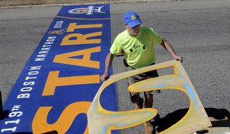 "FILE - In this April 15, 2015, file photo, Boston Marathon start line painter Jacques LeDuc lifts the stencil for the letter ""S"" as he paints the line in Hopkinton, Mass. LeDuc, who painted it for nearly four decades, is retiring from the task. The Boston Athletic Association said it will search for a replacement to paint the line ahead of the April 16, 2018 race. (Ken McGagh/The Metro West Daily News via AP, File)/"
