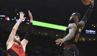 Cleveland Cavaliers forward LeBron James, right, goes up for a dunk on Portland Trail Blazers center Jusuf Nurkic, left, during the first half of an NBA basketball game in Portland, Ore., Thursday, March 15, 2018. (AP Photo/Steve Dykes)