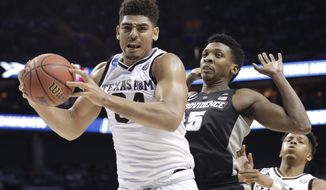 Texas A&M's Tyler Davis (34) grabs a rebound against Providence's Rodney Bullock (5) during the first half of a first-round game in the NCAA men's college basketball tournament in Charlotte, N.C., Friday, March 16, 2018. (AP Photo/Gerry Broome)