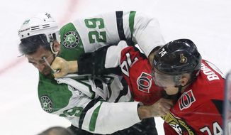 Ottawa Senators defenseman Mark Borowiecki (74) and Dallas Stars defenseman Greg Pateryn (29) trade punches during the first period of an NHL hockey game Friday, March 16, 2018, in Ottawa, Ontario. (Fred Chartrand/The Canadian Press via AP)