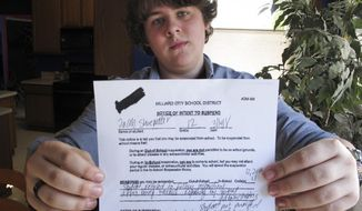 Jacob Shoemaker, 18, holds a copy of his school suspension slip at his home, March 16, 2018, in Hilliard, Ohio. An Ohio high school student says he tried to remain nonpolitical during school walkouts over gun violence and was suspended for a day because he stayed in a classroom instead of joining protests or the alternative, a study hall. Hilliard senior Jacob Shoemaker's citation for not following instructions was shared online, prompting a flood of angry messages to the phone number it had for his father. Some people thought Jacob was suspended for walking out, or mistook his father for the principal. (AP Photo/Kantele Franko)