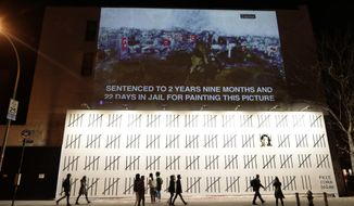 People pass by a mural by British graffiti artist Banksy protesting the imprisonment of Turkish artist Zehra Dogan Friday, March 16, 2018, in New York. Banksy has created the New York mural protesting the imprisonment of Dogan, an ethnic Kurd jailed after painting the Turkish flag flying over the rubble of a destroyed town. (AP Photo/Frank Franklin II)