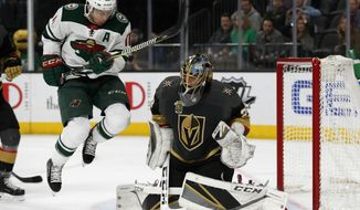 Vegas Golden Knights goaltender Marc-Andre Fleury, right, blocks a shot beside Minnesota Wild left wing Zach Parise during the first period of an NHL hockey game, Friday, March 16, 2018, in Las Vegas. (AP Photo/John Locher)
