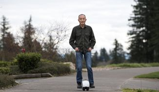 Camas-based inventor Shane Chen says he barely saw any profits from the hover board craze he helped start in 2015 with his invention, the Hovertrax. Knockoffs flooded the market and a typo in his patent later foiled attempts to sue. Here he demonstrates his latest invention, the IOTATrax, that he hopes to better protect, outside his office at Inventist in Camas, Wash., on Monday, March 5, 2018. (Alisha Jucevic/The Columbian via AP)