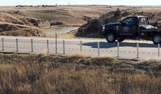 In this Tuesday, Dec. 5, 2017 photo, a vehicle drives near an area where water diverted from the Platte River would flow from a canal on the near side of Nebraska Highway 23 into the canyons on the far side of the road and into Turkey Creek in Smithfield, Neb. (David Hendee/Omaha World-Herald via AP)