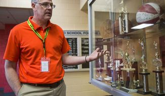 "In this Feb. 7, 2018, photo, administrator Brian Darcy shows off the trophy case at the Idaho School for the Deaf and the Blind in Gooding, Idaho. ""(When) budgets cut, in every school, athletics is the first thing to go,"" said Brian Darcy, the IESDB administrator. ""It was for us, too."" Through enthusiastic messaging and government backing, ISDB avoided closure. (Pat Sutphin/The Times-News via AP)"