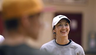 In a March 9, 2018 photo, former Division I college softball player and North Valley High School baseball coach Kelsey Anchors  laughs with members of her team as they discuss their practice session in the school's main gym in Merlin, Oregon. Anchors is believed to be the first woman to lead a high school varsity baseball team in Oregon history. (Scott Stoddard/The Daily Courier via AP)
