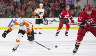 Philadelphia Flyers' Matt Read (24) reaches for a puck as Carolina Hurricanes' Trevor van Riemsdyk (57) watches during the first period of an NHL hockey game in Raleigh, N.C., Saturday, March 17, 2018. (AP Photo/Ben McKeown)
