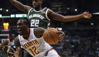 Atlanta Hawks' Taurean Prince drives past Milwaukee Bucks' Khris Middleton during the second half of an NBA basketball game Saturday, March 17, 2018, in Milwaukee. (AP Photo/Morry Gash)