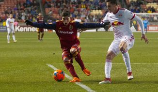 Real Salt Lake forward Jefferson Savarino (7) and New York Red Bulls defender Aaron Long (33) go for the ball during an MLS soccer match in Sandy, Utah, Saturday, March 17, 2018. (Jacob Wiegand/The Deseret News via AP)