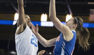 American guard Emily Kinneston, right, shoots as UCLA forward Monique Billings, left, defends during the first half of a first-round game in the NCAA women's college basketball tournament, in Los Angeles, Saturday, March 17, 2018. (AP Photo/Kyusung Gong)