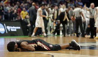 Florida State guard Terance Mann lies on the court in the second half of a first-round game against Missouri in the NCAA college basketball tournament in Nashville, Tenn., Friday, March 16, 2018. Florida State won 67-54. (AP Photo/Mark Humphrey)