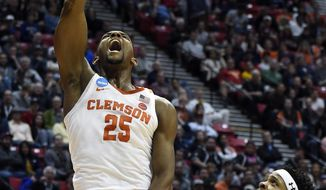 Clemson forward Aamir Simms (25) dunks as New Mexico State forward Jemerrio Jones (10) watches during the first half of a first-round NCAA college basketball tournament game Friday, March 16, 2018, in San Diego. (AP Photo/Denis Poroy)
