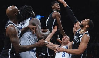 Dallas Mavericks' Kyle Collinsworth (8) fights for a loose ball with Brooklyn Nets' Jahlil Okafor, right, during the first half of an NBA basketball game, Saturday, March 17, 2018, in New York. (AP Photo/Andres Kudacki)