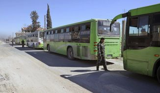 This photo released by the Syrian official news agency SANA, shows Syrian troops stand guard near buses carrying Syrian citizens who were fleeing from fighting between the Syrian government forces and rebels, near Hamouria in eastern Ghouta, a suburb of Damascus, Syria, Friday, March. 16, 2018. The government offensive has pushed further into eastern Ghouta, chipping away at one of the largest and most significant opposition bastions since the early days of the rebellion, communities where some 400,000 people are estimated to be holed up. (SANA via AP)