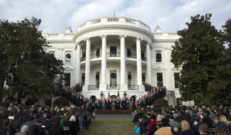 FILE - In this Dec. 20, 2017, file photo, President Donald Trump, surrounded by members of congress and supporters, speaks during an event on the South Lawn of the White House in Washington, to acknowledge the final passage of tax overhaul legislation by Congress. The new tax law ends a benefit long prized by business for schmoozing with customers or courting new ones. And the impact could be felt in big glitzy boxes at sports stadiums, or even at minor league games in small towns with loyal company backers. (AP Photo/Carolyn Kaster, File)