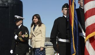 Ship's sponsor Annie Mabus, daughter of 75th Secretary of the Navy Ray Mabus, is escorted to the guests platform for the commissioning ceremony of the Virginia-class fast attack submarine USS Colorado (SSN 788) at Naval Submarine Base New London in Groton, Conn. Saturday, March 17, 2018. Mabus passes between the USS Colorado and the JROTC color guard from Wideview High School in Colorado Springs, Colo. on the way to the platform. (Dana Jensen/The Day via AP)