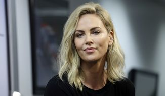 Actress Charlize Theron listens to a question during a news conference before the NASCAR Daytona 500 Cup series auto race at Daytona International Speedway in Daytona Beach, Fla., Sunday, Feb. 18, 2018. (AP Photo/Terry Renna)