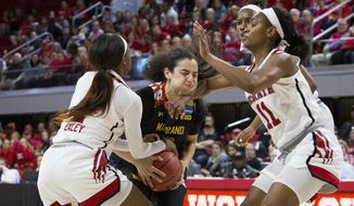 Maryland's Eleanna Christinaki (10) attempts to drive between North Carolina State's Kiara Leslie (11) and North Carolina State's Kaila Ealey, left, during the first half of a second-round game in the NCAA women's college basketball tournament in Raleigh, N.C., Sunday, March 18, 2018. (AP Photo/Ben McKeown)