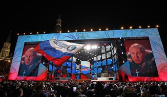Russian President Vladimir Putin speaks during a rally near the Kremlin in Moscow, Sunday, March 18, 2018. An exit poll suggests that Vladimir Putin has handily won a fourth term as Russia's president, adding six more years in the Kremlin for the man who has led the world's largest country for all of the 21st century. (AP Photo/Pavel Golovkin)
