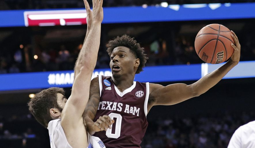 Texas A&M's Jay Jay Chandler (0) drives against North Carolina's Luke Maye (32) during the first half of a second-round game in the NCAA men's college basketball tournament in Charlotte, N.C., Sunday, March 18, 2018. (AP Photo/Gerry Broome)