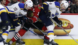 Chicago Blackhawks center Jonathan Toews, center, battles for the puck against St. Louis Blues center Brayden Schenn, left, and defenseman Carl Gunnarsson during the second period of an NHL hockey game Sunday, March 18, 2018, in Chicago. (AP Photo/Nam Y. Huh)