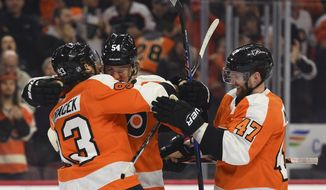 Philadelphia Flyers' Oskar Lindblom, center, is congratulated by Jakub Voracek, left, and Andrew MacDonald after scoring a goal during the second period of an NHL hockey game against the Washington Capitals, Sunday, March 18, 2018, in Philadelphia. (AP Photo/Derik Hamilton)