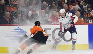 Washington Capitals' John Carlson, right, controls the puck past Philadelphia Flyers' Travis Sanheim during the first period of an NHL hockey game, Sunday, March 18, 2018, in Philadelphia. (AP Photo/Derik Hamilton)