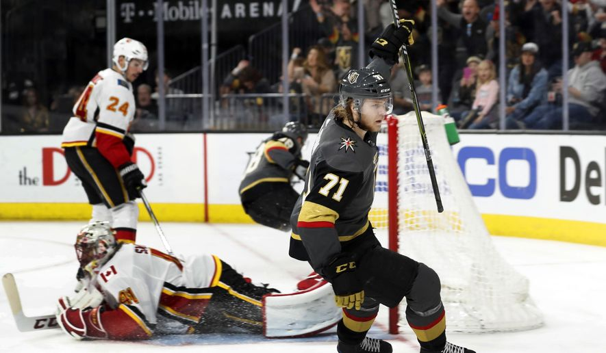 Vegas Golden Knights center William Karlsson (71) celebrates a goal past Calgary Flames goaltender Mike Smith (41) during an NHL hockey game Sunday, March 18, 2018, in Las Vegas. Flames defenseman Travis Hamonic (24) is in the background. It was Karlsson's third goal of the game. (AP Photo/Steve Marcus)
