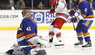 New York Islanders goaltender Jaroslav Halak (41) of Slovakia reacts as Carolina Hurricanes left wing Jeff Skinner (53) celebrates after Hurricanes defenseman Jaccob Slavin, not shown, scored a goal during the first period of an NHL hockey game in New York, Sunday, March 18, 2018. New York Islanders defenseman Nick Leddy (2) watches, at right. (AP Photo/Kathy Willens)
