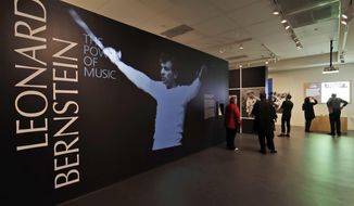 In this Wednesday, March 14, 2018 photo, journalists walk through the Leonard Bernstein exhibit during a press preview at the National Museum of American Jewish History in Philadelphia. The exhibit on the acclaimed composer and conductor opens March 16 and runs through Sept. 2, 2018. (AP Photo/Matt Slocum)
