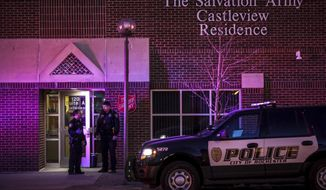 Emergency personnel respond to the scene of a fatal stabbing Saturday, March 17, 2018, at the Salvation Army Castleview Residence in downtown Rochester, Minn. Police have arrested a man in the multiple fatal stabbings at a Salvation Army apartment building in Minnesota. (Joe Ahlquist/The Rochester Post-Bulletin via AP)