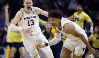 Michigan guard Jordan Poole (2) is chased by forward Moritz Wagner (13) after Poole made a 3-point basket at the buzzer to win an NCAA men's college basketball tournament second-round game against Houston on Saturday, March 17, 2018, in Wichita, Kan. Michigan won 64-63. (AP Photo/Charlie Riedel) ** FILE **