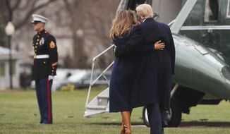 President Donald Trump holds first lady Melania Trump who lost her footing while walking across the South Lawn of the White in Washington, Monday, March 19, 2018, before boarding Marine One helicopter for the short trip to Andrews Air Force Base, Md. Trump is traveling to Manchester, N.H., to announced his plan to combat opioid drug addiction. (AP Photo/Pablo Martinez Monsivais)
